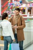Fotografie dívka s nákupní tašky mluvit usmívající se muž v obchoďáku