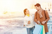 Fotografie attractive girl with disposable cup and handsome man with shopping bags smiling and looking at each other in parking
