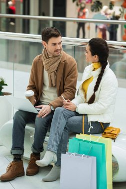 handsome man with laptop and paper cup and girl with smartphone and shopping bags sitting on bench in mall
