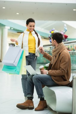 handsome man with laptop and disposable cup sitting on bench and holding hand of girl with girl with shopping bags in mall