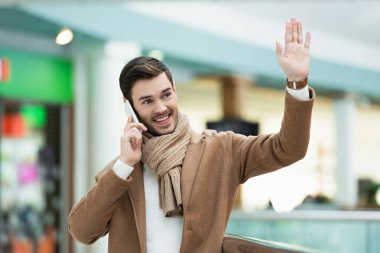 Smiling man talking on smartphone and waving with hand stock vector
