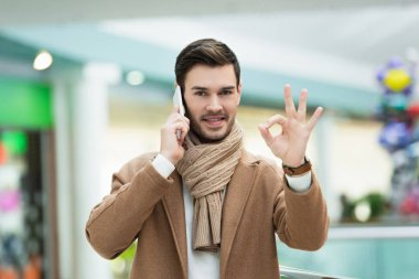Handsome man talking on smartphone and showing ok sign stock vector