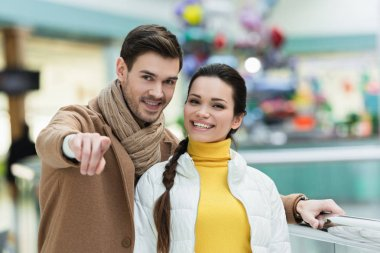 handsome man pointing with finger at camera ad smiling girl in shopping mall