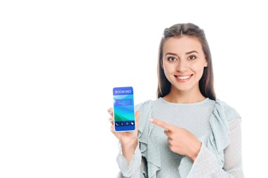smiling woman showing smartphone with booking lettering isolated on white