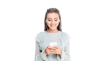 portrait of cheerful woman using smartphone while listening music in earphones isolated on white