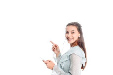 side view of smiling woman with smartphone pointing away while listening music in earphones isolated on white
