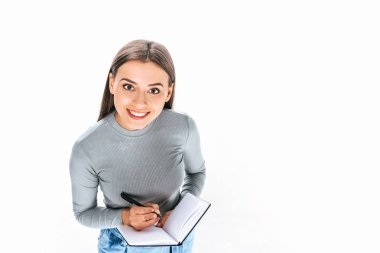 high angle view of smiling woman with notebook and pen isolated on white