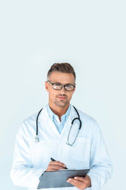 Handsome doctor in glasses with stethoscope on shoulders writing something in clipboard and looking at camera isolated on white stock vector