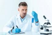 hezký vědec pohledu na zkumavky s modrým činidel izolované na bílém