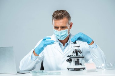 handsome scientist in medical mask and medical gloves making experiment isolated on white