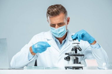 handsome scientist in medical mask and medical gloves making test with microscope isolated on white