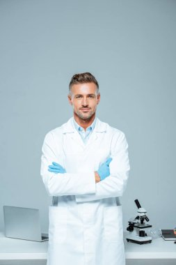 handsome scientist in white coat and latex gloves standing with crossed arms and looking at camera isolated on white