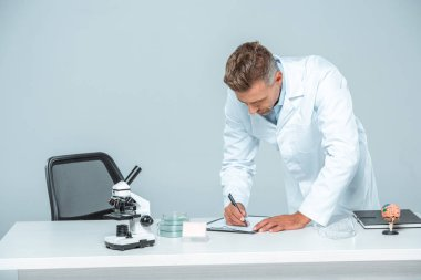 handsome scientist writing something to clipboard at table isolated on white