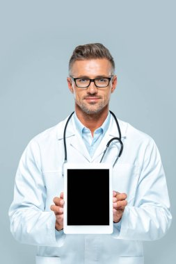 Handsome doctor with stethoscope showing tablet with blank screen and looking at camera isolated on white stock vector
