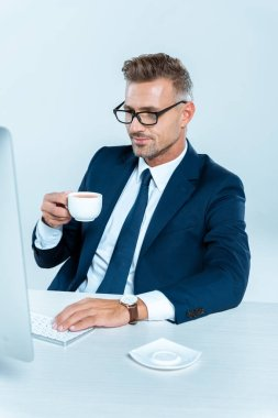 handsome cheerful businessman holding cup of coffee and looking at computer isolated on white