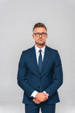 handsome businessman in suit and glasses looking at camera isolated on white