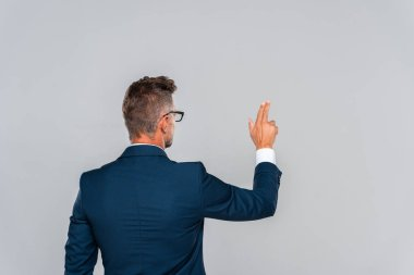 back view of businessman in glasses touching something isolated on grey, artificial intelligence concept