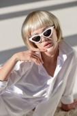 vysoký úhel pohledu smyslná blondýnka v sluneční brýle a módní zimní oblek sedí na kabát z umělé kožešiny na bílém