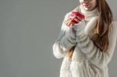 zugeschnittenes Bild der Frau in modischer Winter Pullover und Schal Tasse Tee isoliert auf grau