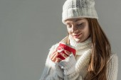 Fotografie attractive woman in fashionable winter sweater and scarf holding cup of tea isolated on grey