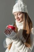 schöne Mädchen in stilvollen Winter Pullover und Schal Tasse Tee isoliert auf grau