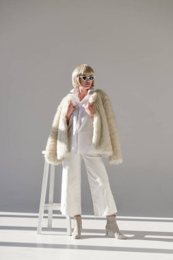 Beautiful blonde girl in sunglasses and fashionable winter outfit with faux fur coat standing on white stock vector