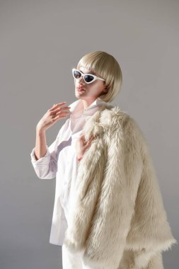 portrait of attractive blonde woman in sunglasses and fashionable winter outfit with faux fur coat isolated on white