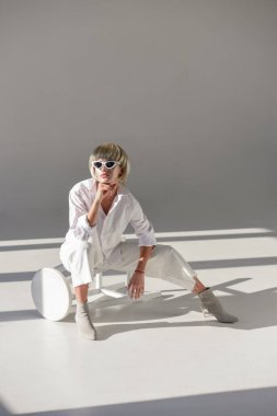 Attractive blonde woman in sunglasses and fashionable white outfit sitting on chair and resting chin on hand on white stock vector