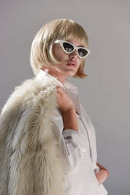 Portrait of attractive blonde woman in sunglasses and fashionable winter outfit with faux fur coat looking away isolated on white stock vector