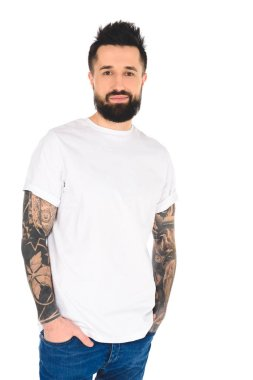 handsome bearded man with tattoos and hands in pockets looking at camera isolated on white