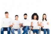 Fotografia gruppo multiculturale sorridente dei giovani utilizzando computer portatili isolati su bianco