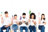 Fotografie multiethnic group of young people using smartphones and holding flags isolated on white