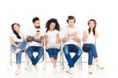 mnohonárodnostní skupiny mladých lidí, kteří používají miniaplikace, zatímco muž, který držel kávu jít izolované na bílém