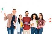 Veselá multikulturní skupina lidí s vlajkami různých zemí izolované na bílém úsměvem