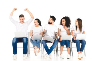 Handsome young man rejoicing with hands above head while multiethnic group of people using laptops isolated on white stock vector