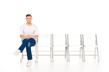 Handsome young man sitting with crossed legs isolated on white stock vector