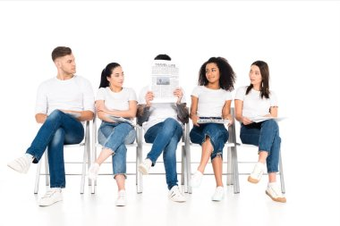 Multiethnic group of young people sitting on chairs with crossed legs and looking at man with newspaper and obscure face isolated on white stock vector