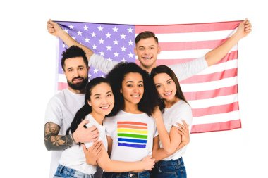 multiethnic group of young people smiling and hugging while holding flag of usa isolated on white