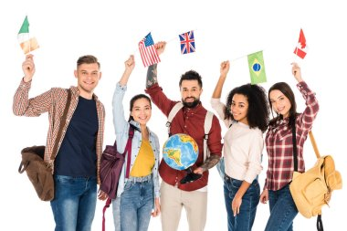 handsome man holding globe and standing with multiethnic group of people holding flags of different countries above heads isolated on white