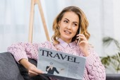 Photo pretty woman sitting on sofa, talking on smartphone and holding travel newspaper in living room