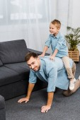 smiling boy sitting on back of father standing on all fours and looking at camera in living room