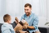apa és fia ül a kanapén, és a gazdaság mackó nappaliban mosolyogva