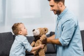 smiling father and son holding teddy bear in living room