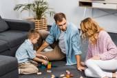 rodiče a syna hrát s dřevěných bloků na podlahu v obývacím pokoji