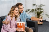 Fotografie smiling man sitting on sofa, holding remote controller and embracing wife with striped popcorn bucket