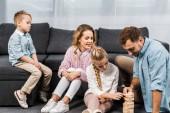 Fotografia due genitori felici giocando legno blocchi Torre di gioco con la figlia sul pavimento mentre ragazzo upset che si siede sul divano nel soggiorno