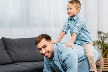 Father standing on all fours and looking at camera while cute boy sitting on back in apartment stock vector