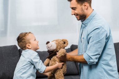 Smiling father and son holding teddy bear in living room stock vector