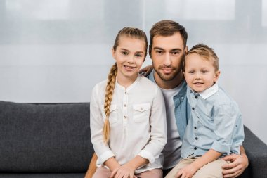smiling father with cute children sitting on sofa and looking at camera in apartment