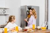 lány asztalnál ül és nézi anyja megnyitása hűtőszekrény
